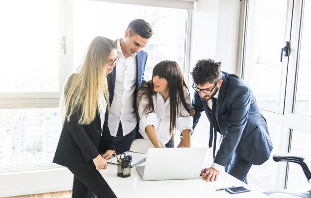 grupo-de-empresarios-de-pe-no-escritorio-olhando-para-laptop-no-escritorio