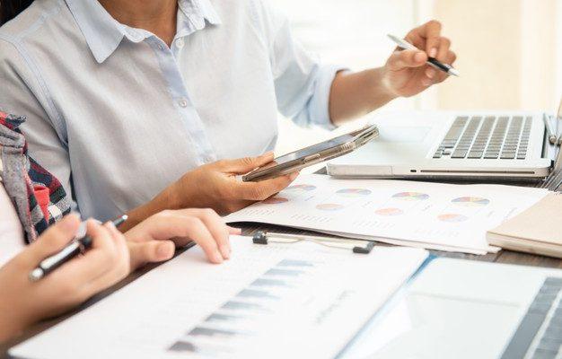 processo-de-trabalho-em-equipe-empresarios-discutindo-as-tabelas-e-graficos