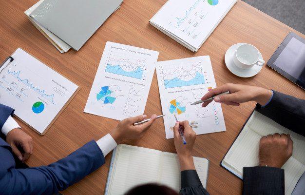 top-shot-de-tres-empresarios-irreconheciveis-sentado-na-reuniao-e-olhando-para-graficos